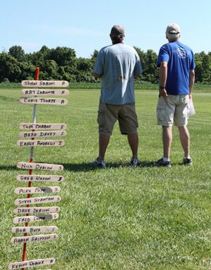 A pilot and spotter stand in the background In the foreground is a stick with clothespins on it. A name in each, it's used as the score board.